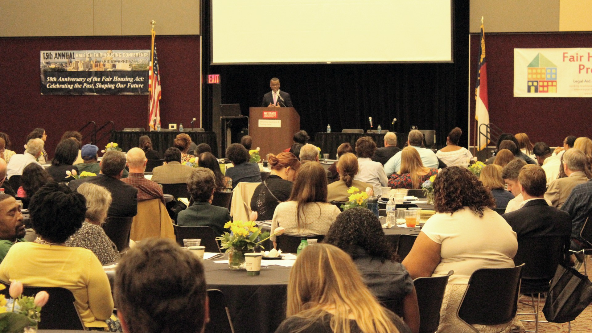 Seated crowd viewing speaker at fair Housing Conference