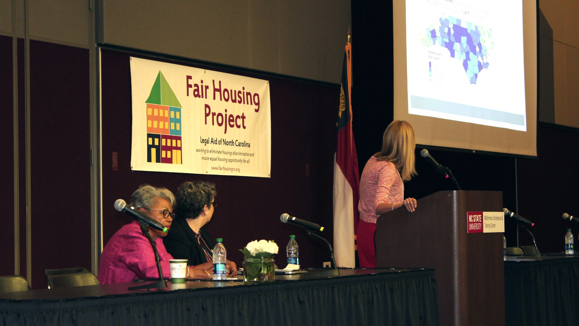 Woman leading panel at fair housing conference