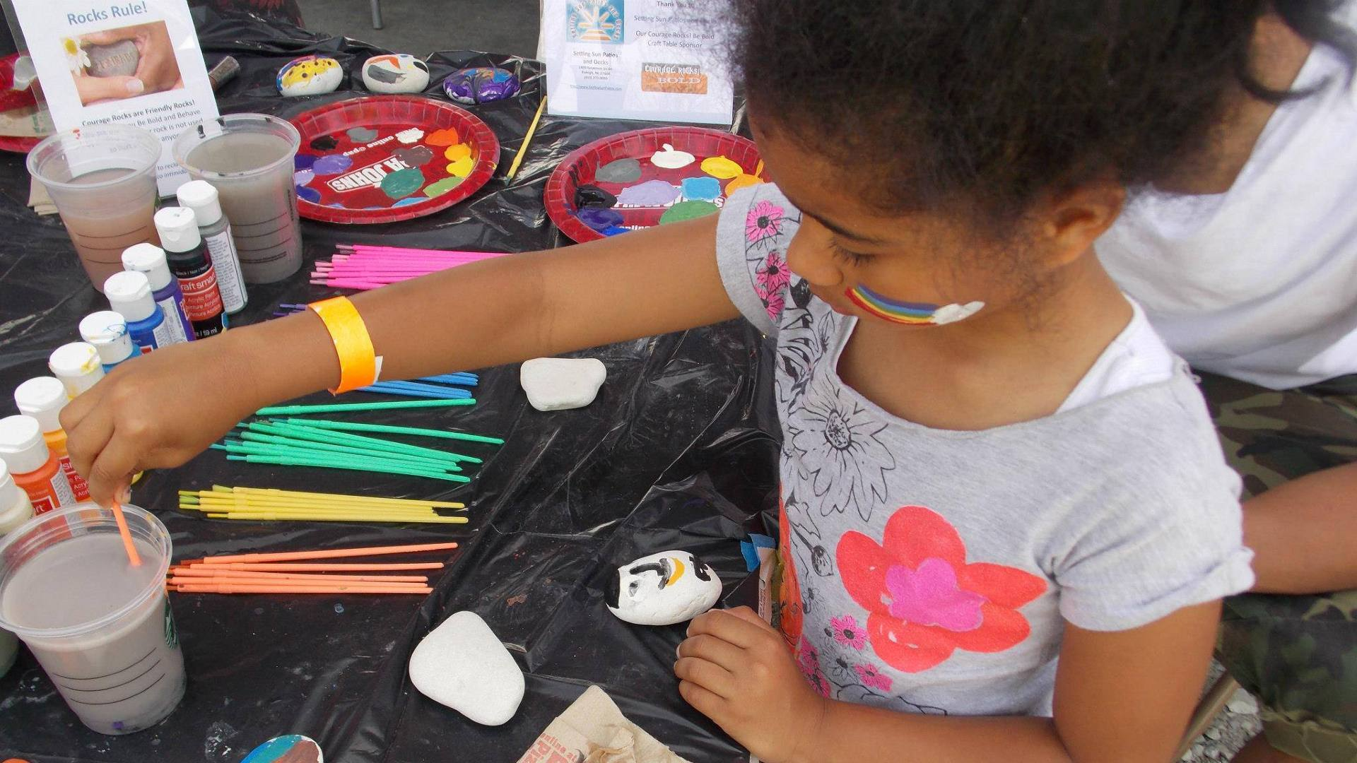 A girl paints rocks at a local event