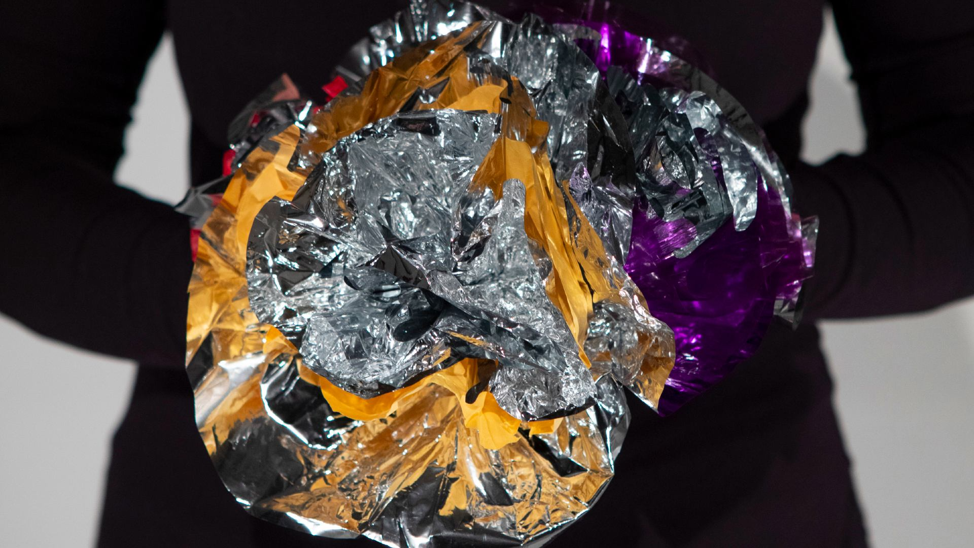 person holding a silver, gold, and purple mylar flower
