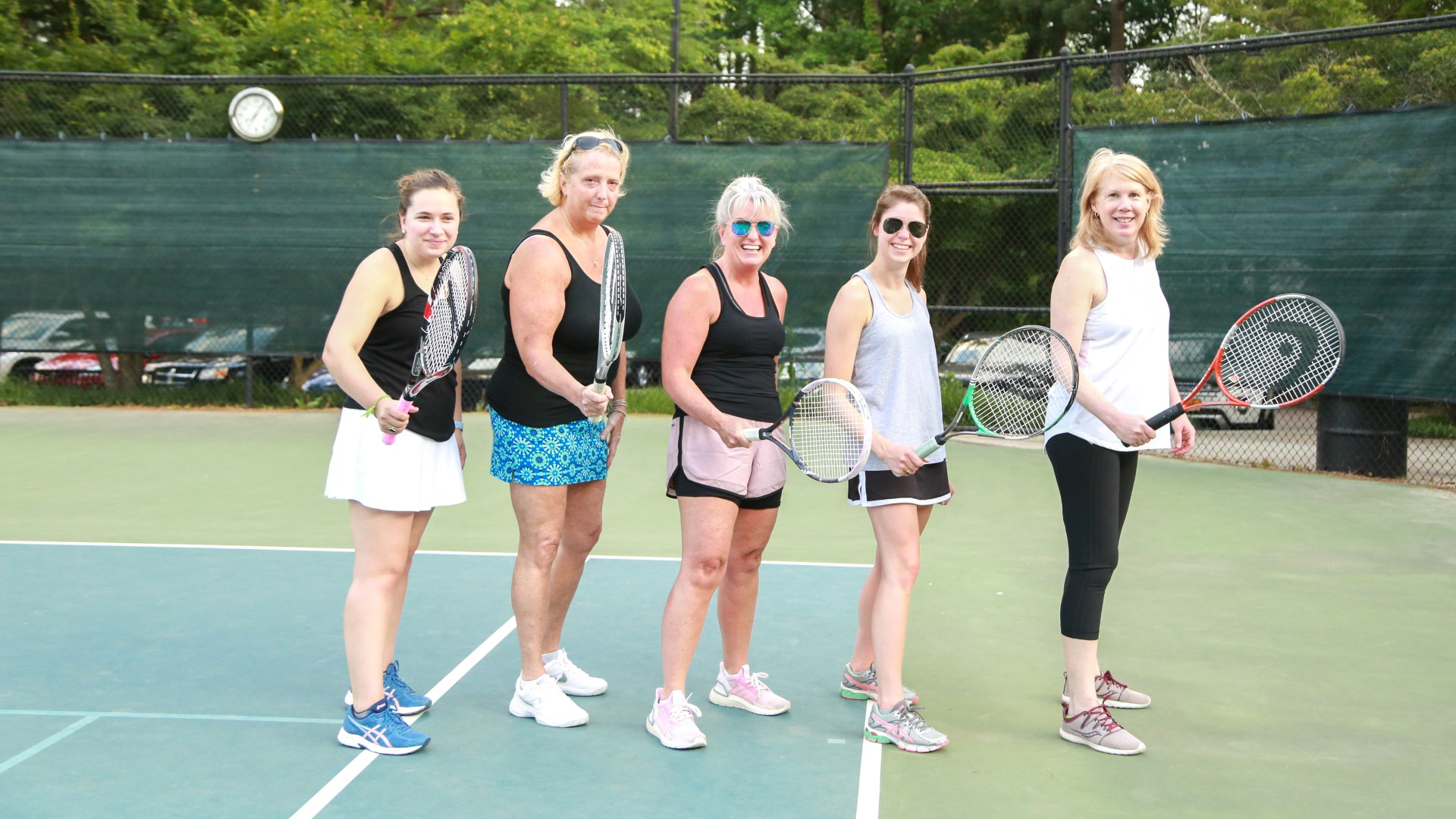 Group of adults posing for a picture on the tennis court
