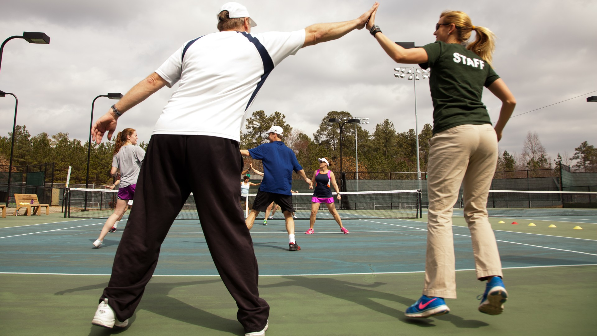 Adults participating in adult cardio on tennis courts