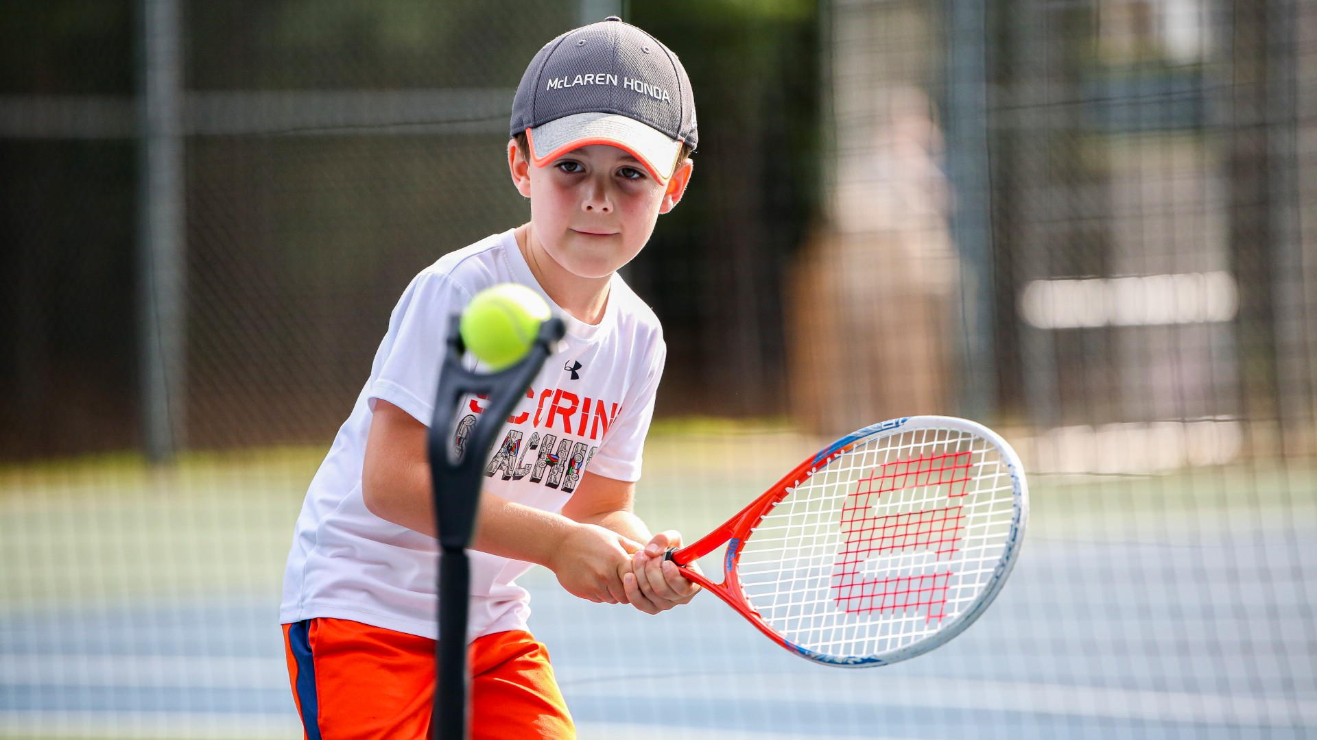 A young kid playing tennis