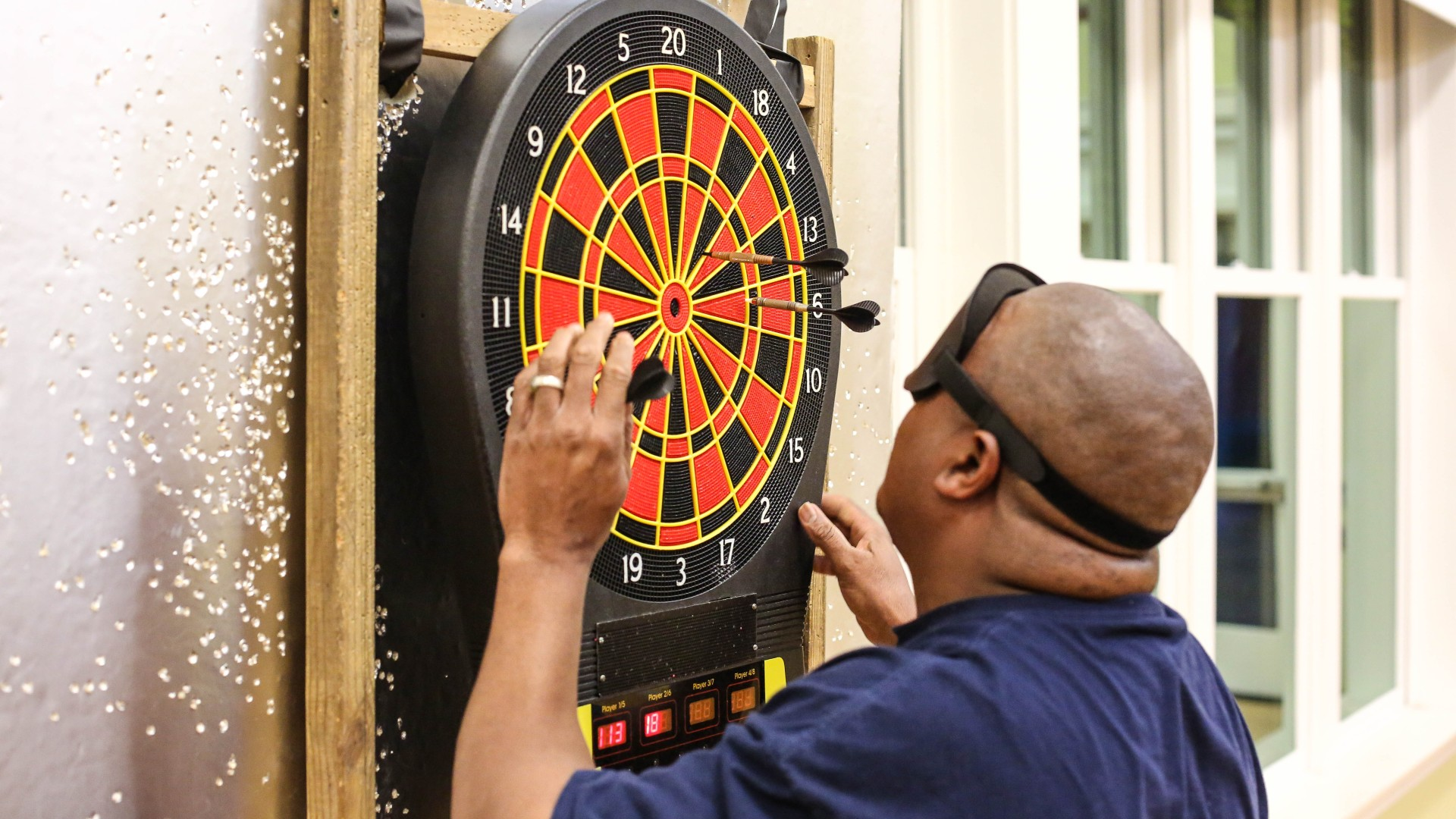 A person playing darts as part of an SRIS program