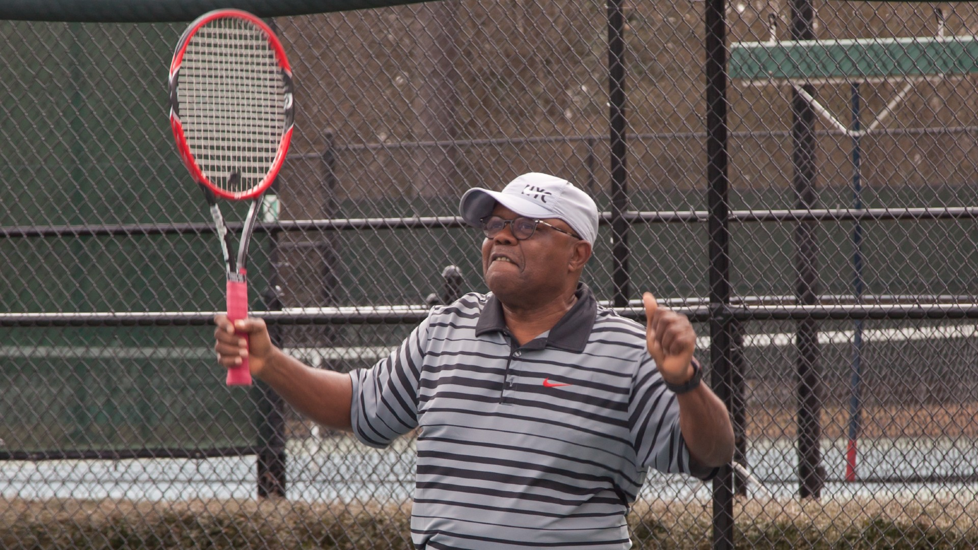 An older adult playing tennis