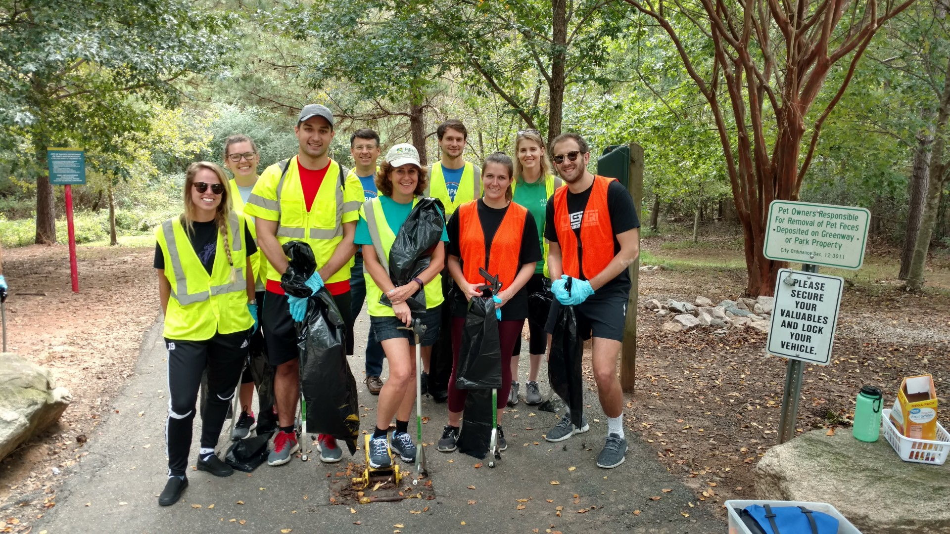 A group of park volunteers cleaning up along a greenway trail