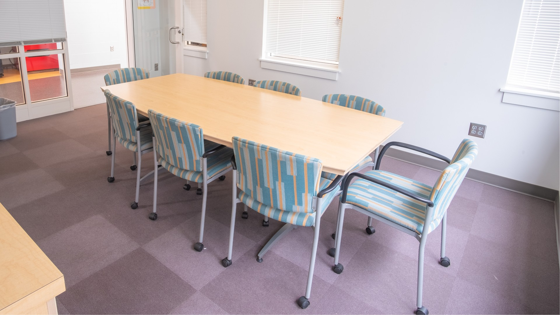 A conference room with a large table and eight chairs