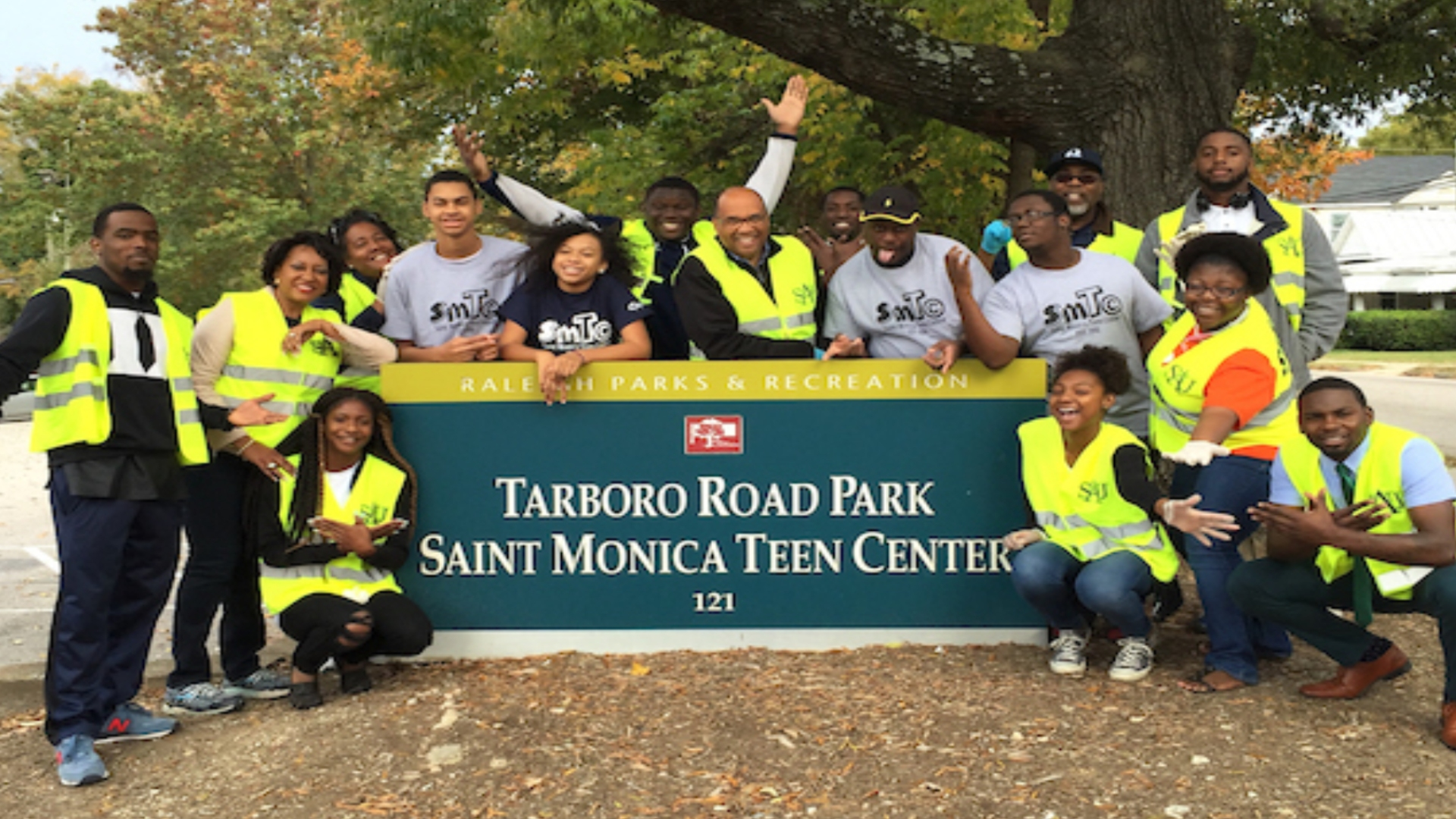 A group of park volunteers posing in front of the Tarboro Road Park sign