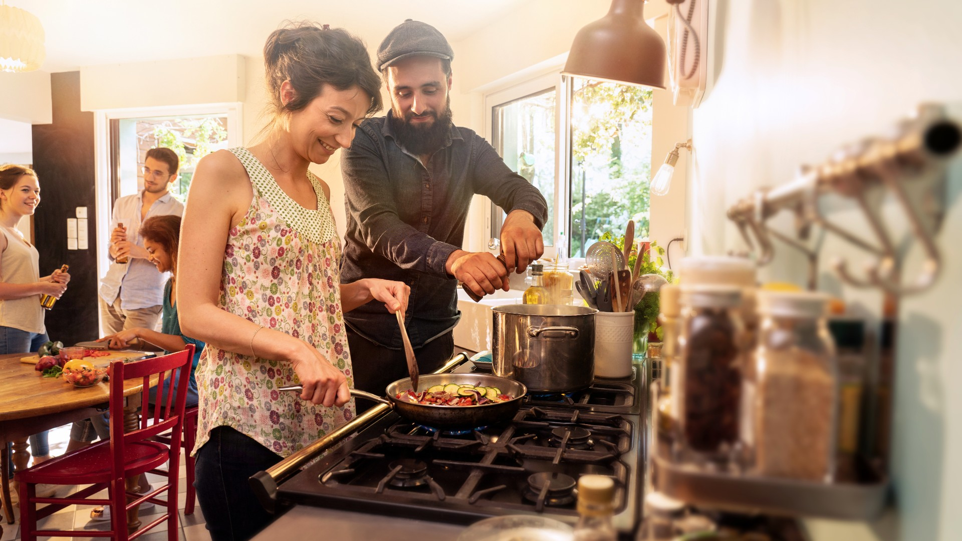 couple cooking with friends at kitchen table