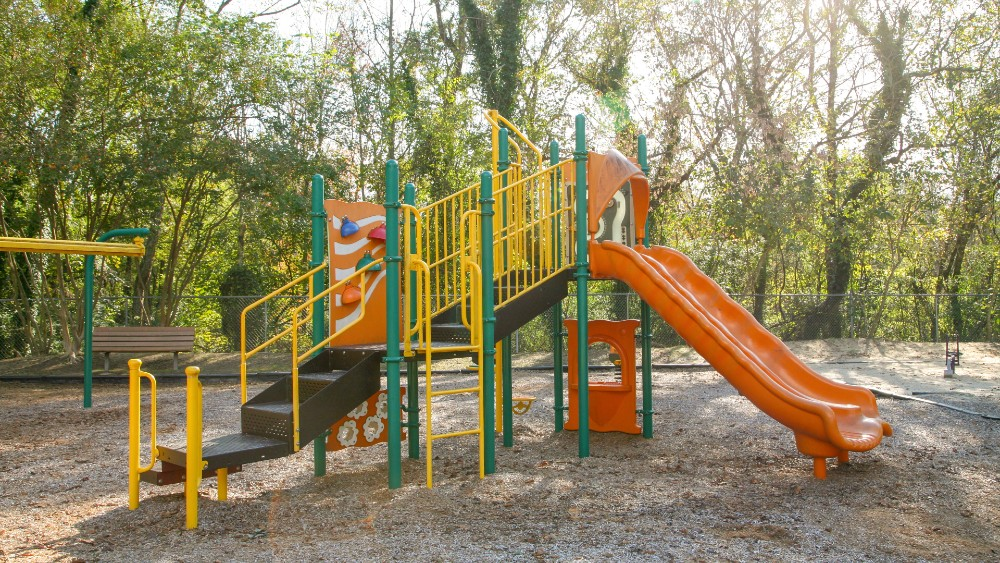 Playground structure with slide and climbing stairs ladder in bright orange, yellow and green