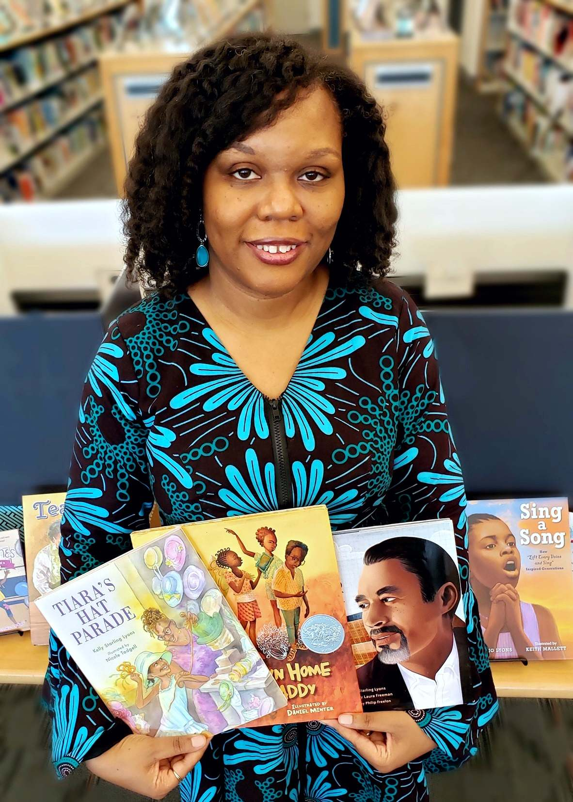 2021 Piedmont Laureate Kelly Starling Lyons holds a few of her books