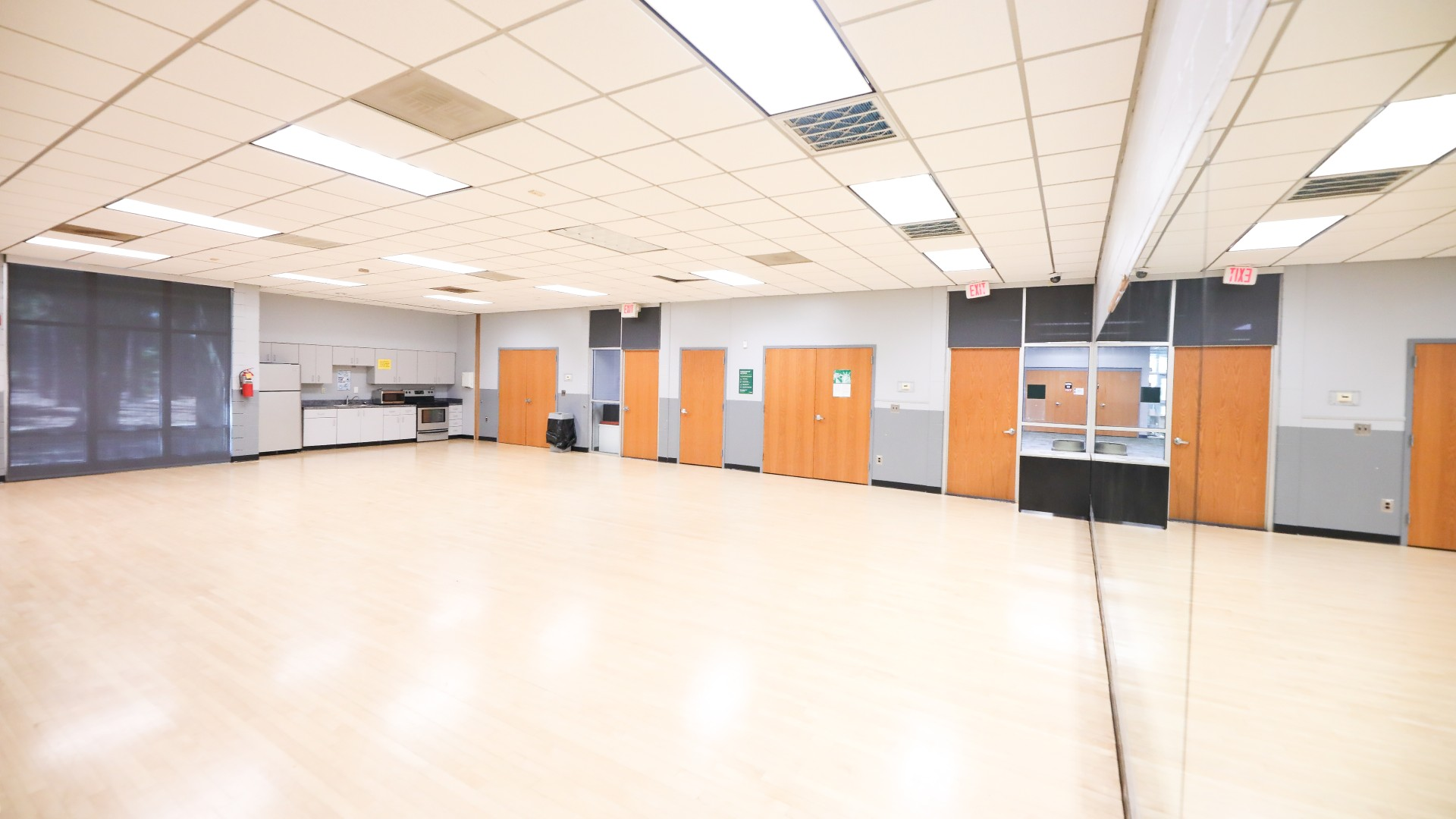 A large open dance studio type room with hardwood floors and a large mirorr.