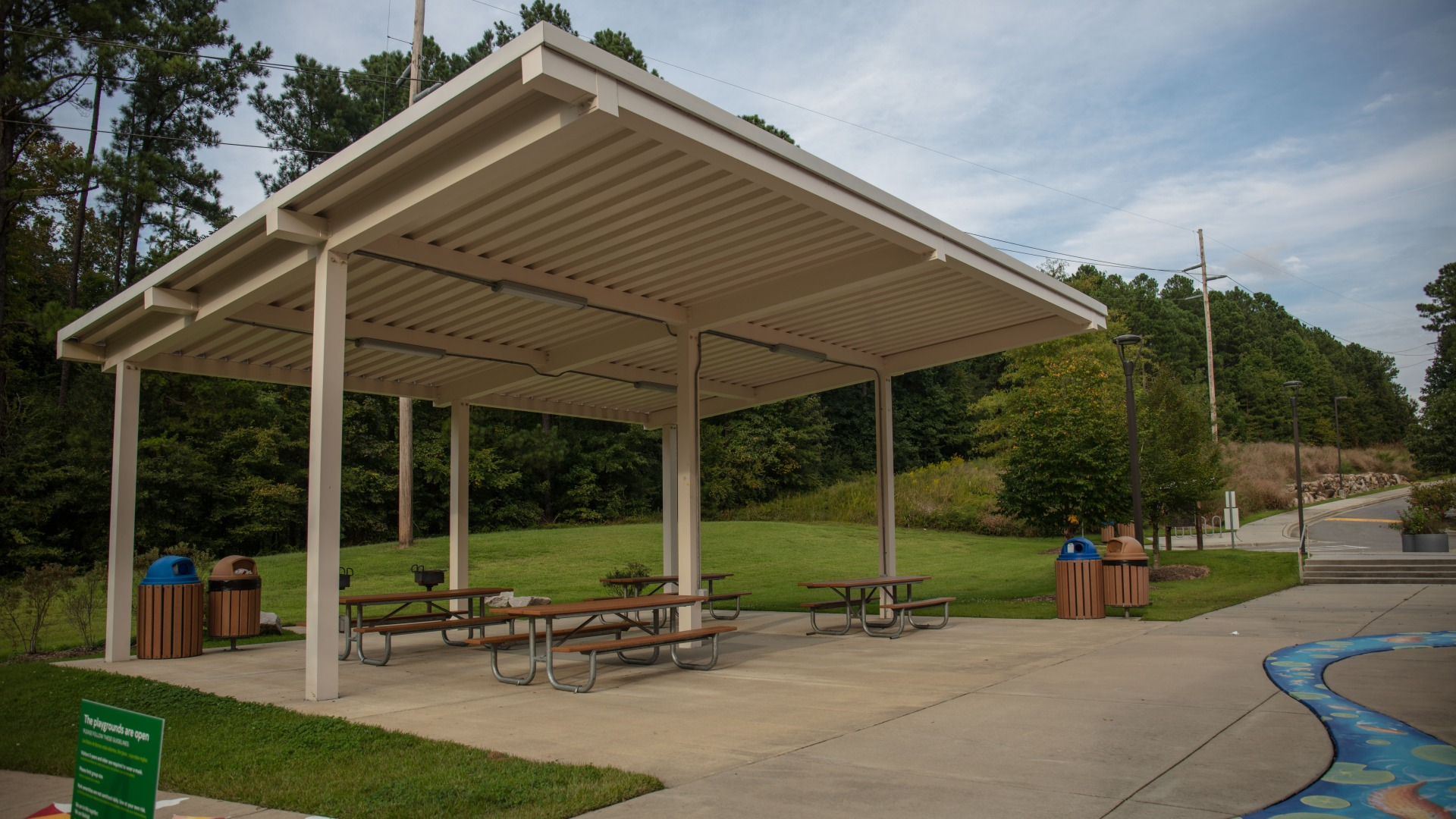 A medium size open-air picnic shelter with several picnic tables