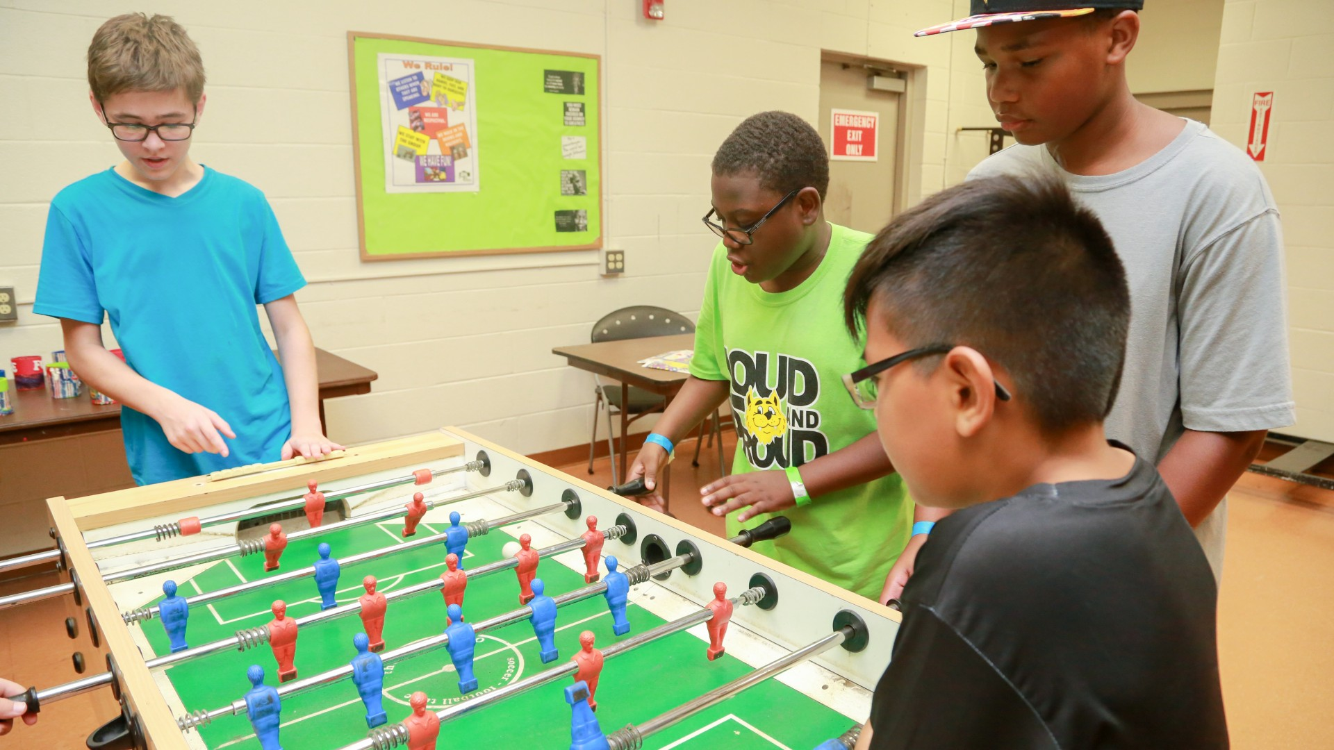 A group of young kids playing foosball together at Lions Park