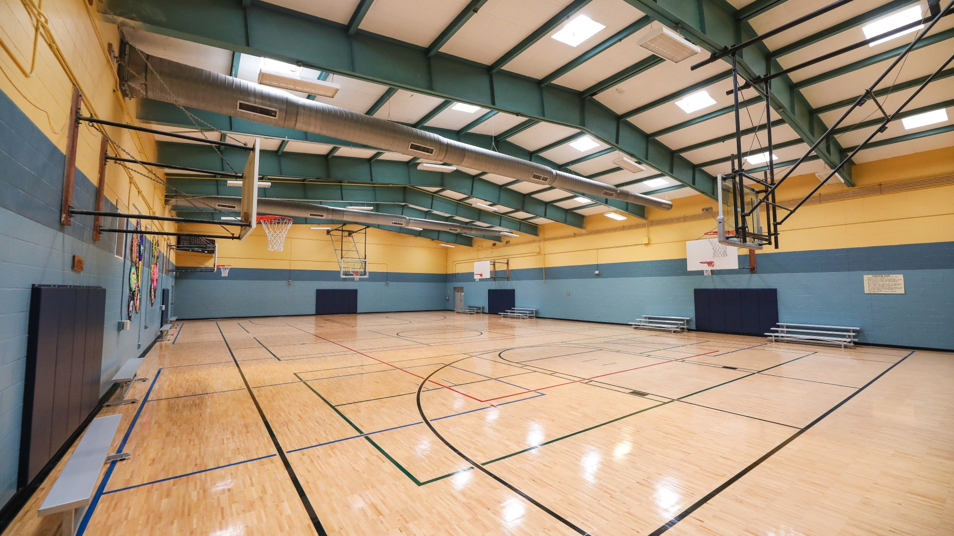 A large open gymnasium with multiple hoops and bleachers