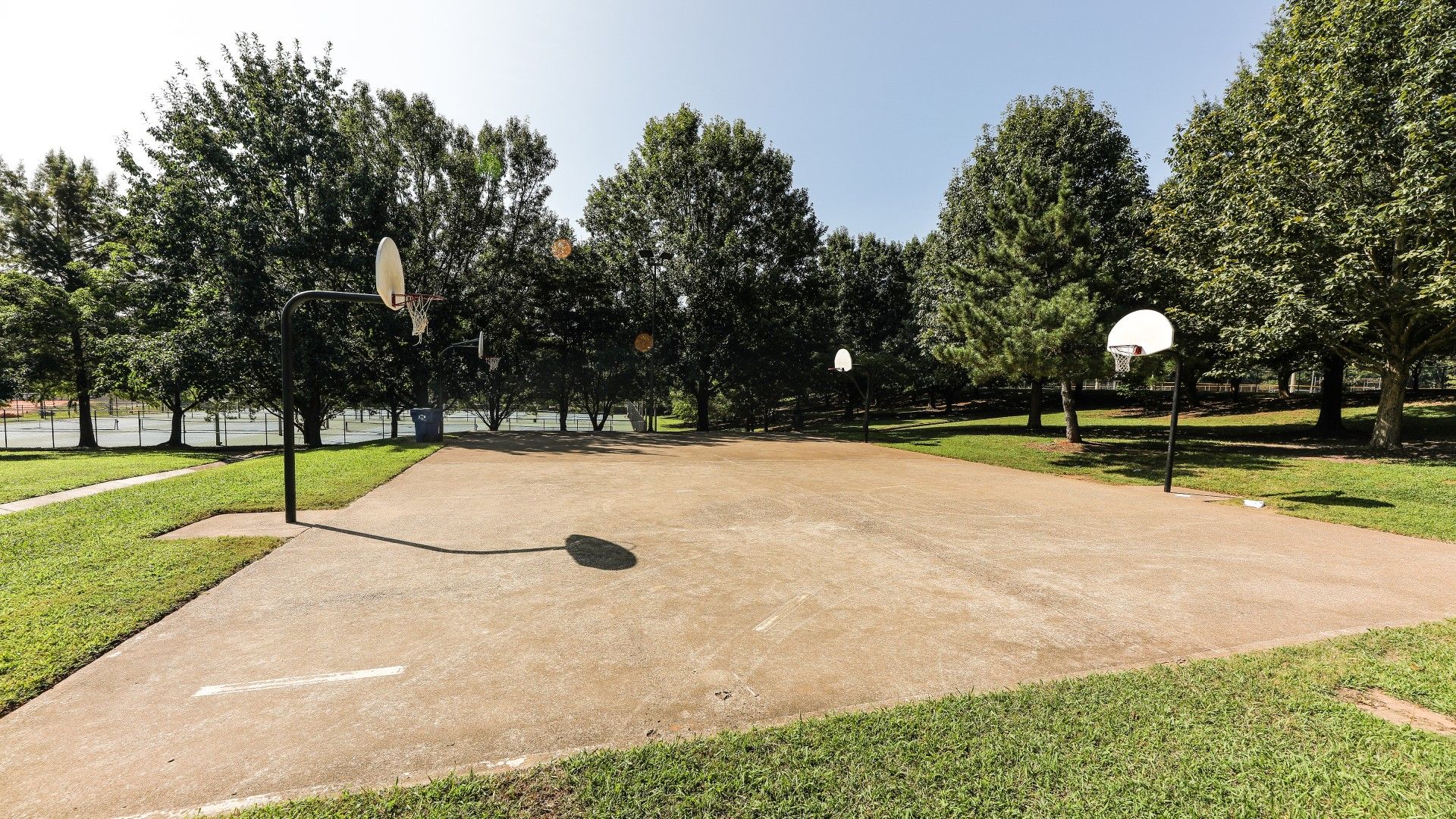Two outdoor lighted basketball courts with a concrete surface