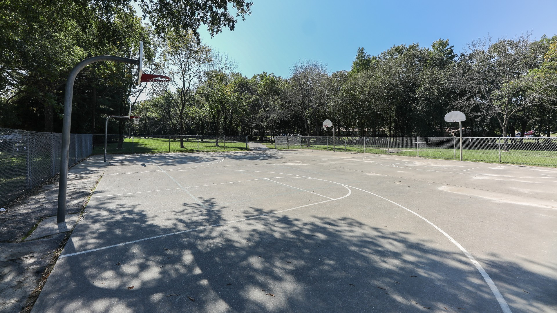 A concrete outdoor basketball court with four hoops total