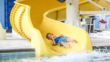 boy holding his nose going down a slide before hitting the pool inside the Buffaloe Road Aquatic Center