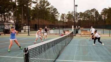 Women batting the ball back and forth at Millbrook Exchange Tennis courts