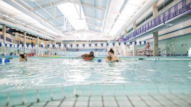 Parents teaching tots to swim at Pullen Park Pool