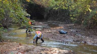 A volunteer picks up trash in a Raleigh stream to help reduce water pollution in our area.