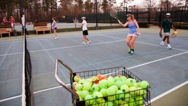 Women hitting tennis balls on tennis courts