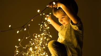 Child playing with holiday lights