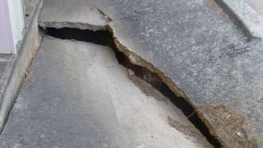 A crack in pavement from a failing stormwater pipe that's close to the entrance of a storage facility