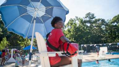 female lifeguard sitting in lifeguard chair at biltmore pool smiling with view of pool in the background