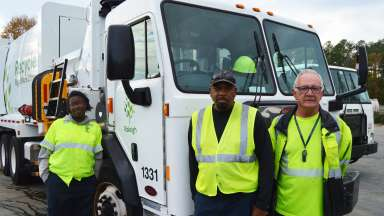two male and one female recycling crew employees in front of the truck