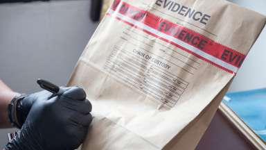 Man writing in black sharpie on an evidence bag