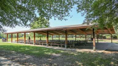 A very large picnic shelter with several tables located near the restrooms at Anderson Point Park