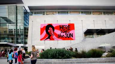 "Large scale crocheted portrait of Nina Simone with the words ""Here Comes the Sun"" hanging on the outside of the Raleigh Convention Center."