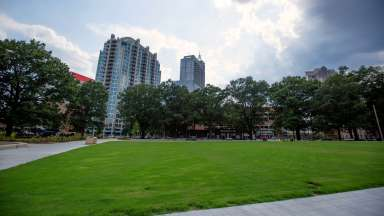 A view of part of the open lawn at Moore Square with the city buildings in the background