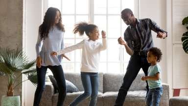 Family dancing in house having fun