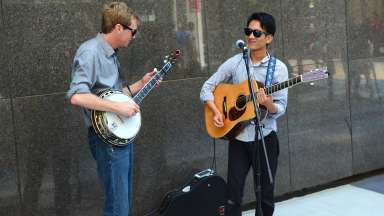 guitar player and banjo player performing in a plaza in downtown raleigh