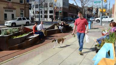 man walking dog through parklet downtown