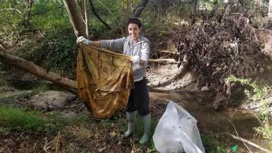A smiling volunteer cleaning up a stream in Raleigh.