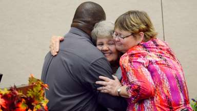 group hugging at mayor's persons with disabilities awards