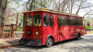 Red historic Raleigh Trolley parked at Mordecai Historic Park in spring
