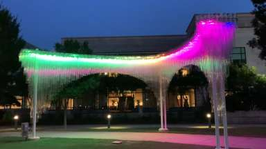 Arches over an outdoor walkway at the Duke Energy Center for the Performing Arts. Hundreds of polycarbonate tubes create an ethereal cloud-like effect during the day and an interactive luminescent sculpture in the evening.