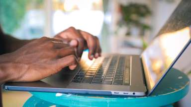 mans hands typing on a laptop