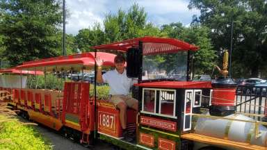 Historic train at Pullen Park Amusements with smiling and waving staff driver