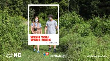 A man and woman walking in a grassy field wearing masks.