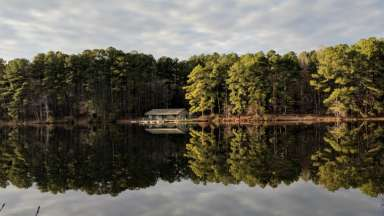 Lake view at Durant Nature Preserve with trees and cabin