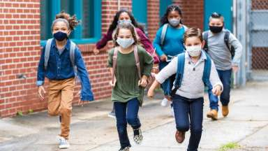 Kids in masks running outside school wearing backpacks
