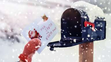 Hand wearing mittens putting letter to Santa in mailbox with snow