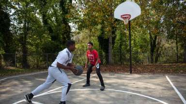 Two teen boys playing basketball on outdoor court at Apollo Heights Park