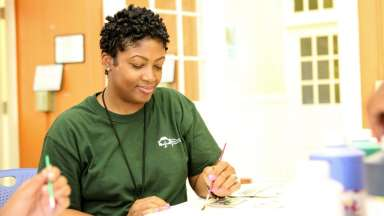 Woman in Raleigh parks staff shirt painting