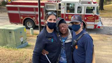 Firefighters with woman in community they helped